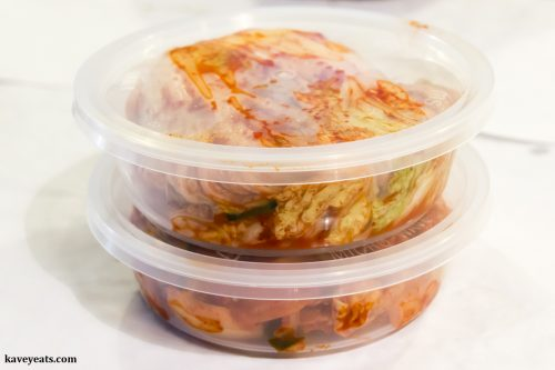 Freshly made kimchi in plastic tubs