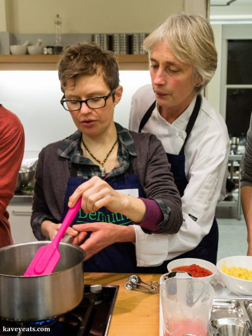 Cooking class tutor helping student