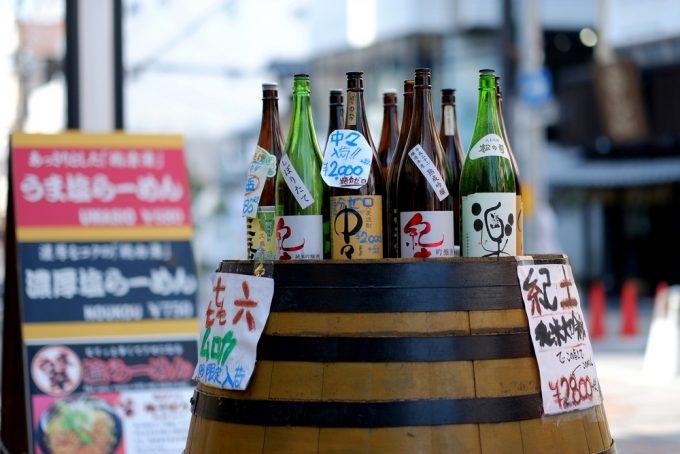 Sake bottles for sale displayed on a barrel