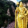 Beautiful golden statue in front of greenery and cliffs in Kuala Lumpur