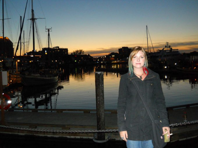 Traveller posing in front of night time harbour scene in Victoria, Canada - 100 Fantastic Cities for City Breaks, as chosen by travel bloggers (part 5)