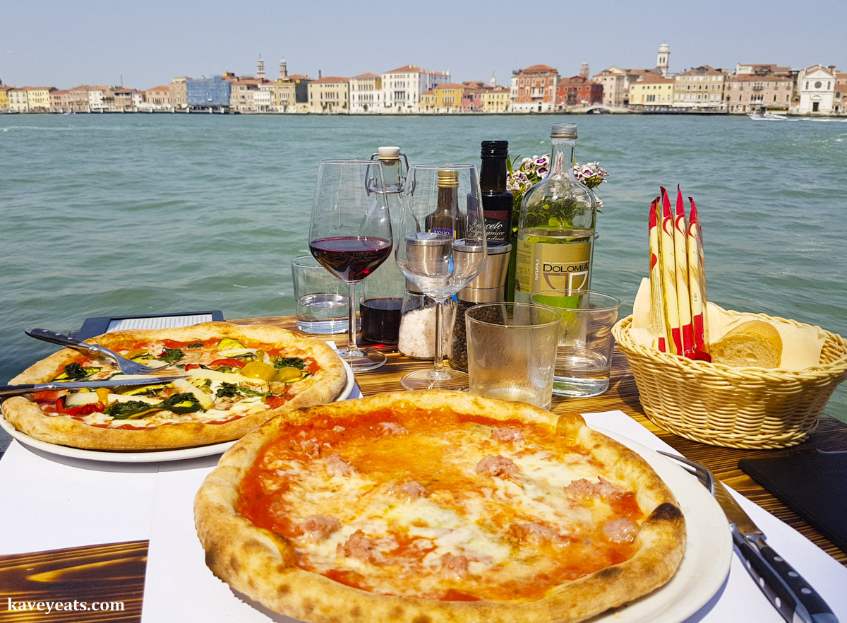 An outdoor table with two pizzas and wine, overlooking the canals and buildings of Venice