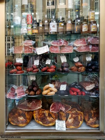 Window display of cured meats in Casa Arcozelo delicatessen in Porto, Portugal.