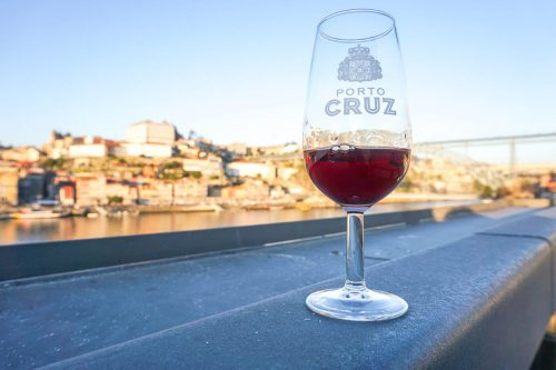 A glass of Port Wine with backdrop of Porto riverside