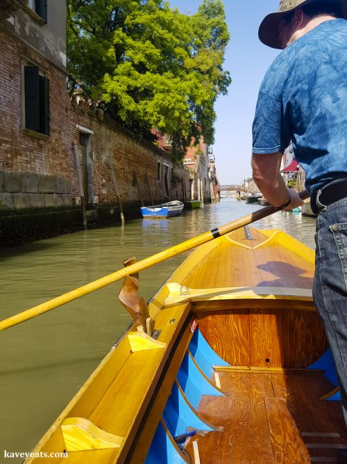 Student rowing a Row Venice batele, a narrow row boat that is similar to a Venetian gondola.