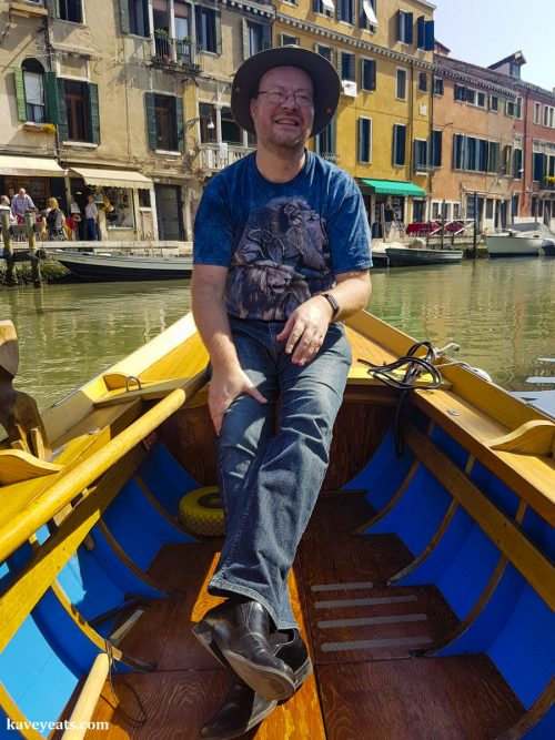 Man in tourist batele taking a rowing lesson in Venice