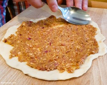 Spreading lamb topping onto dough using the back of a spoon