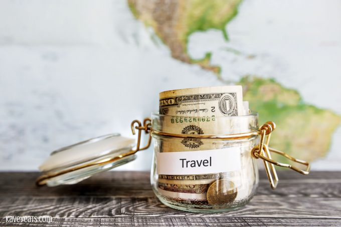 Jar labelled Travel full of folded dollar notes on table in front of world map on wall