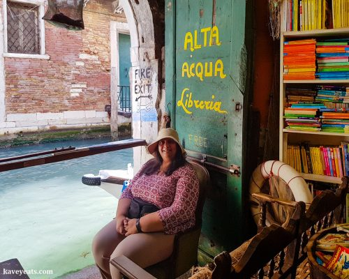 Lady pausing on a chair to rest in a bookshop in Venice Italy