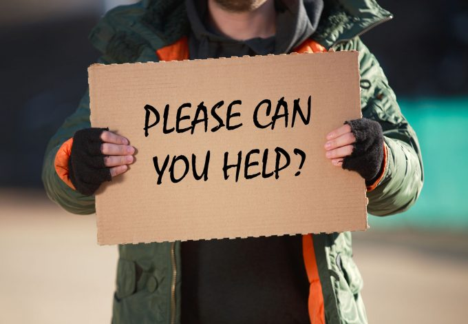 man holding sign that says please can you help?